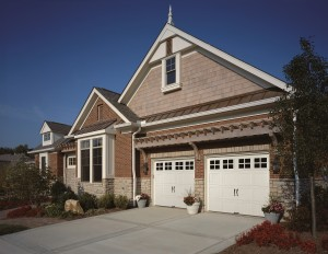 Brick home with double white garage doors